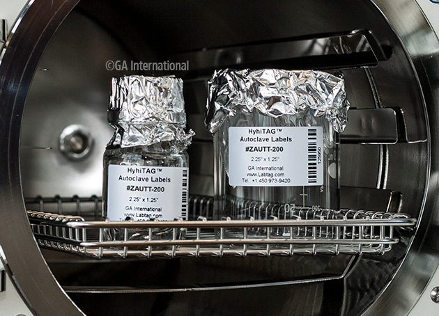 two containers being pulled out of the autoclave machine. they are labelled with the high-temperature resistant labels, printed with information an a barcode