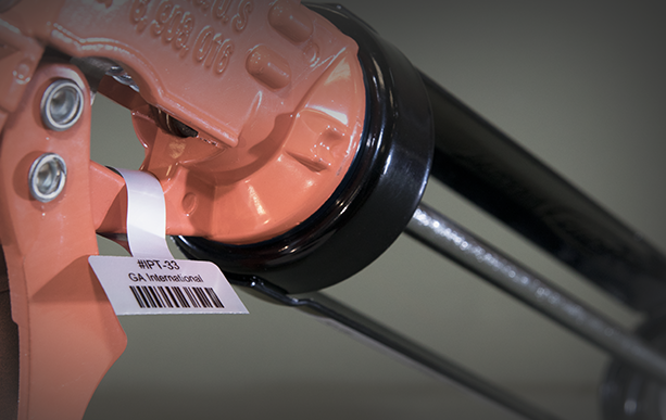 A close-up of a caulking gone tagged with a construction tool identification label printed with alphanumeric text and a 1D barcode.