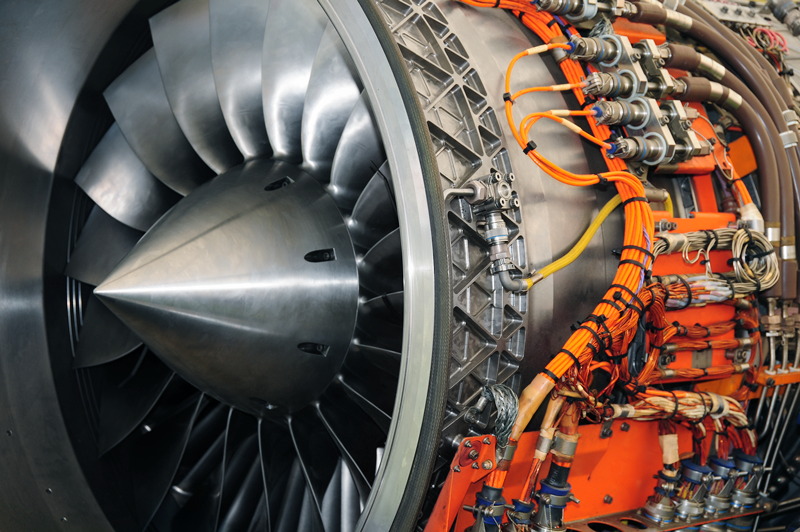 Aircraft turbine engine viewed from the side, with exposed cables, wires, and tubing.