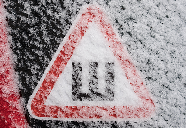 Triangular warning label on the frost-covered glass of a car warning drivers that the car is fitted with wheels with studded rubber.