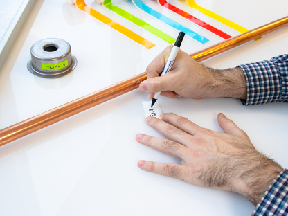 Someone using a water-resistant cryogenic marker to inscribe a piece of white low-temperature tape for metal surfaces, next to a copper pipe.