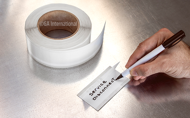 A hand writing on a piece of perforated, self-laminating tape with a black permanent ink marker, next to a roll of the tape.